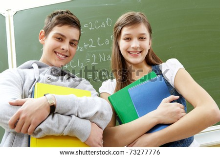 Portrait of happy guy and girl with books looking at camera - stock photo