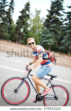 Portrait of happy guy riding bicycle in the park - stock photo