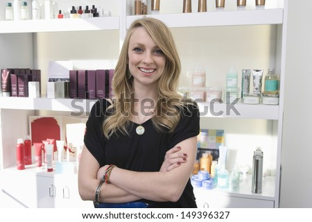 Portrait of happy hairdresser standing arms crossed against shelves at salon - stock photo