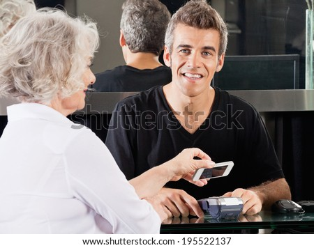 Portrait of happy hairdresser with woman paying through mobile phone at counter using NFC - stock photo