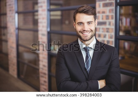 Portrait of happy handsome businessman with arms crossed standing in office - stock photo