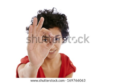 Portrait of happy hispanic girl doing ok sign with hand, smiling at camera - stock photo