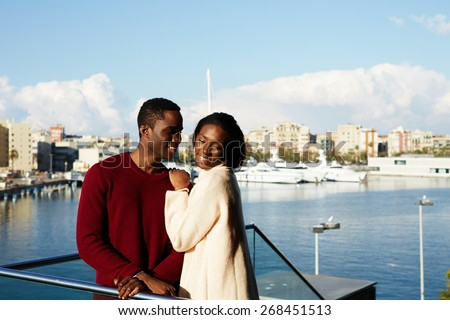 Portrait of happy hugging couple on modern balcony with beautiful port with yachts on background, fashionable couple enjoying each other during vacation holidays in Barcelona - stock photo