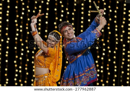 Portrait of happy Indian couple in traditional wear performing Dandiya Raas against neon lights - stock photo