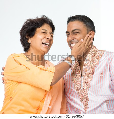 Portrait of happy Indian family having fun conversation at home. Mature 50s Indian mother and her 30s grown son. - stock photo