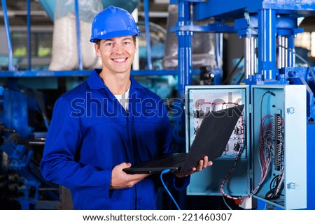 portrait of happy industrial engineer with laptop computer - stock photo