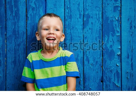 Portrait of happy joyful beautiful little boy against the old textured blue wall - stock photo