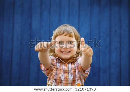 Portrait of happy joyful beautiful little girl against the old textured blue wall gesturing thumb - stock photo