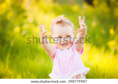 Portrait of happy joyful child in pink dress over wild yellow field flowers background. Family playing together outside. Mom and little daughter cheerfully blowing and catching soap bubbles.  - stock photo