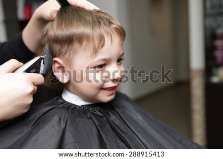 Portrait of happy kid at the barbershop - stock photo