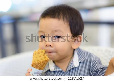 Portrait of happy kid biting ice-cream cone - stock photo