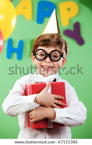 Portrait of happy lad in funny eyeglasses on birthday party with present - stock photo