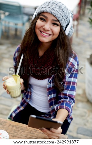 Portrait of happy laughing woman holding tropical fruit cocktail in coffee shop, smiling girl using digital tablet sitting in cafe - stock photo