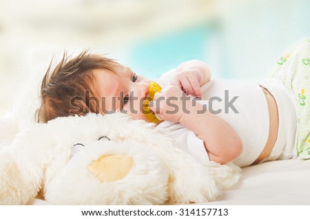 Portrait of happy laying little kid on soft toy - stock photo