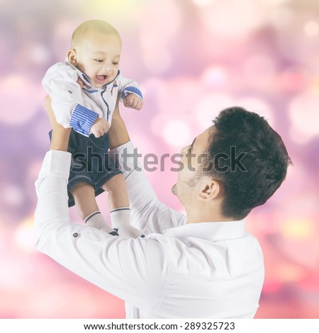 Portrait of happy little baby boy playing with his dad, shot with light glitter background - stock photo