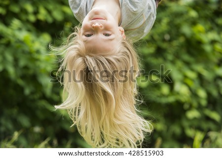 Portrait of Happy little blond girl playing on a rope web playground outdoor. Upside down  - stock photo