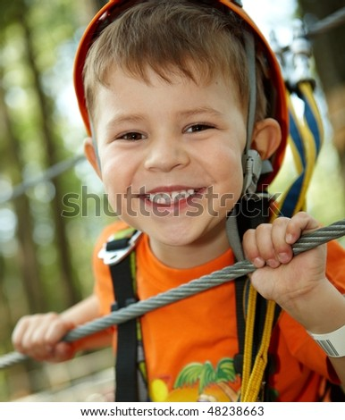 Portrait of happy little boy having fun in adventure park smiling to camera wearing mountain helmet and safety equipment. - stock photo
