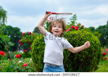 Portrait of happy little boy holding badminton racket and shuttlecock while jumping - stock photo
