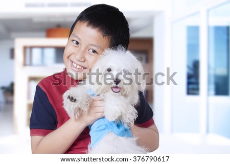 Portrait of happy little boy hugging a maltese dog while smiling at the camera at home - stock photo