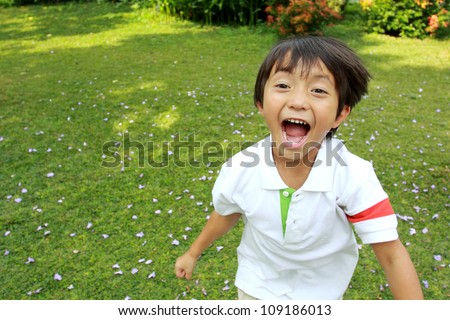 Portrait of happy little boy running in the park - stock photo