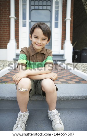 Portrait of happy little boy sitting on front steps of house - stock photo