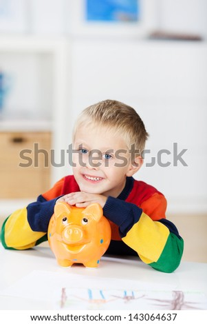 Portrait of happy little boy with piggybank at table in house - stock photo