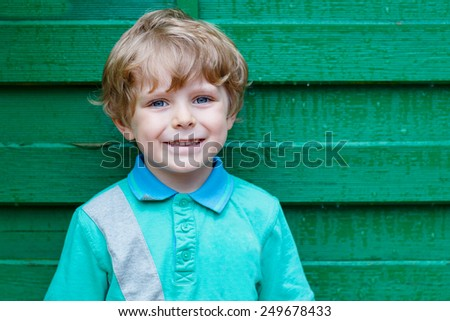 Portrait of happy little cute kid boy with blond hairs and blue eyes against green wooden background in garden - stock photo