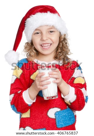 Portrait of happy little girl in pajamas and santa hat with glass of milk isolated on white background - stock photo