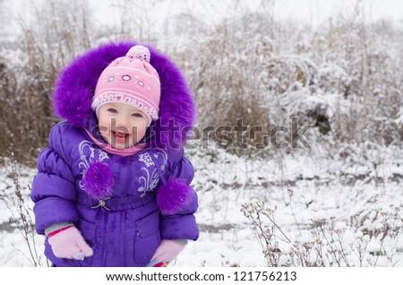 Portrait of happy little girl in snowy landscape - stock photo