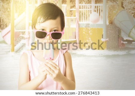 Portrait of happy little girl standing at the pool while wearing sunglasses and enjoy ice cream, shot with an instagram effect - stock photo