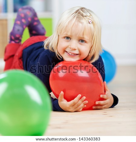 Portrait of happy little girl with balloons lying on floor at home - stock photo