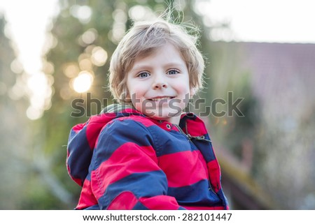 Portrait of happy little kid boy in red jacket, outdoors on sunset. - stock photo