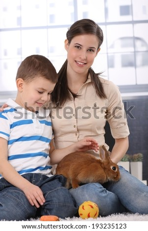 Portrait of happy little kid with mum caressing cute rabbit pet, smiling. - stock photo