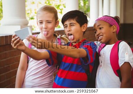 Portrait of happy little school kids taking selfie in school corridor - stock photo