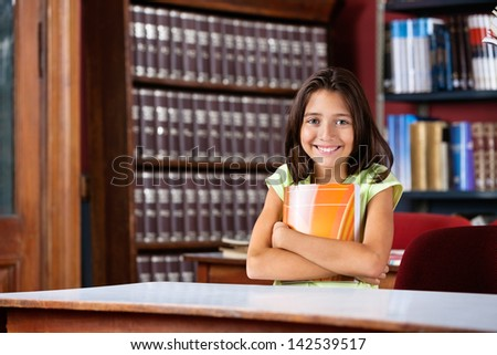 Portrait of happy little schoolgirl holding book while sitting at table in library - stock photo