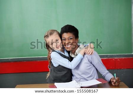 Portrait of happy little schoolgirl hugging teacher at desk in classroom - stock photo