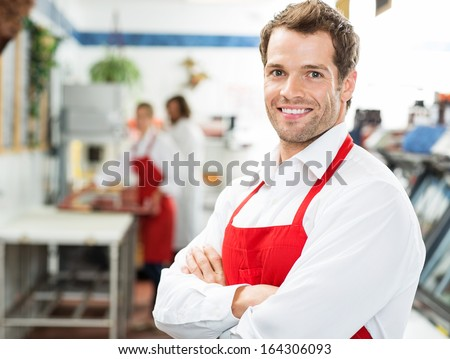 Portrait of happy male butcher standing arms crossed at store with colleagues working in background - stock photo