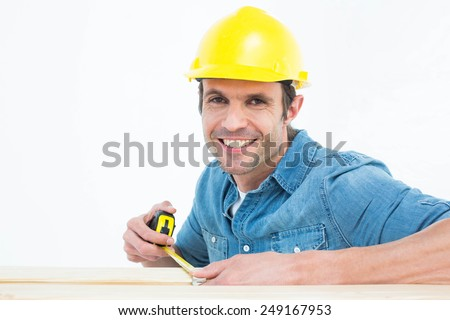 Portrait of happy male carpenter using measue tape over white background - stock photo