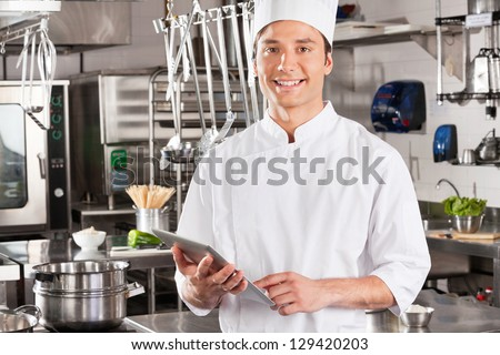Portrait of happy male chef holding tablet computer in commercial kitchen - stock photo