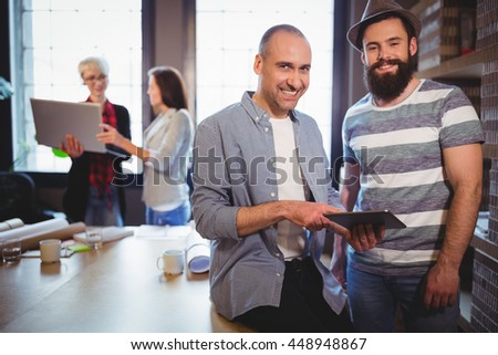 Portrait of happy male colleagues by desk in creative office - stock photo