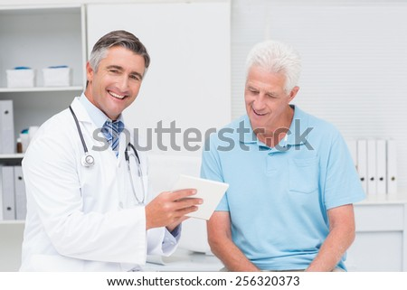 Portrait of happy male doctor explaining prescription to senior man in clinic - stock photo