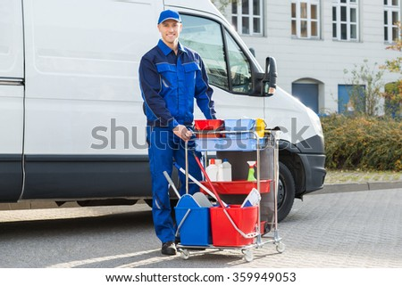 Portrait of happy male janitor standing with cleaning equipment against truck - stock photo