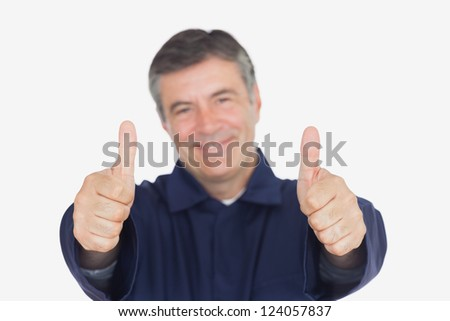 Portrait of happy male mechanic gesturing thumbs up over white background - stock photo