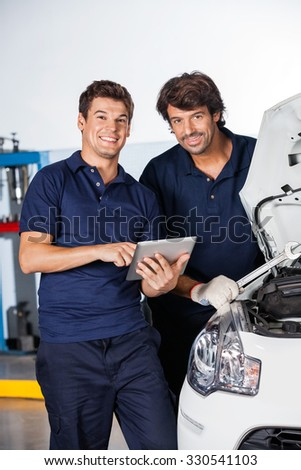 Portrait of happy male mechanics with tablet computer standing by car at auto repair shop - stock photo