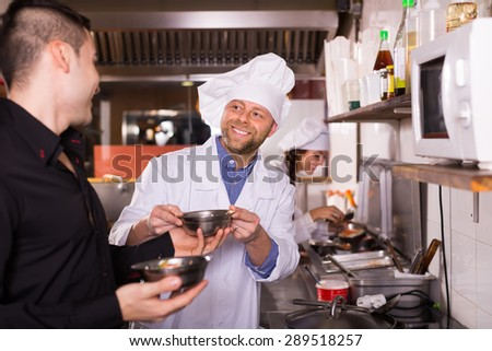 Portrait of happy male waiter holding dishes and cooks at cafe kitchen - stock photo