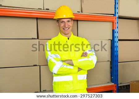Portrait Of Happy Male Warehouse Worker With Arms Crossed In Warehouse - stock photo