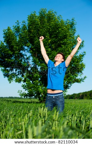 portrait of happy man against tree and blue sky - stock photo
