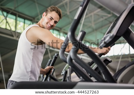 Portrait of happy man exercising on the elliptical machine at gym - stock photo