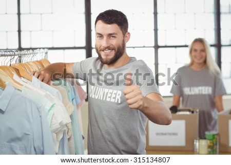 Portrait of happy man gesturing thumbs up while selecting clothes for donation - stock photo