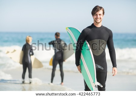 Portrait of happy man holding a surfboard on the beach on a sunny day - stock photo
